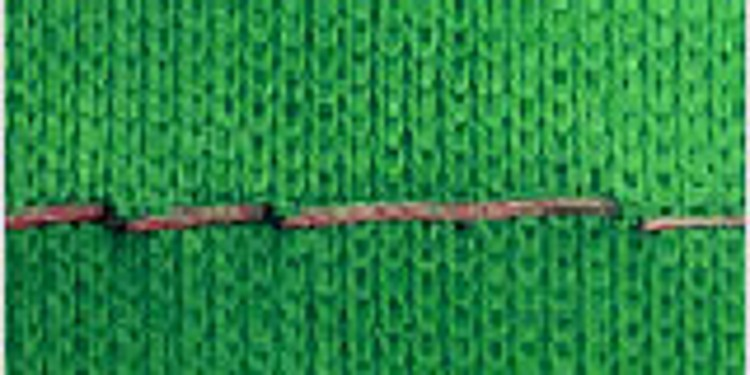 Close-up of a seam on a green knitwear that shows skipped stitches