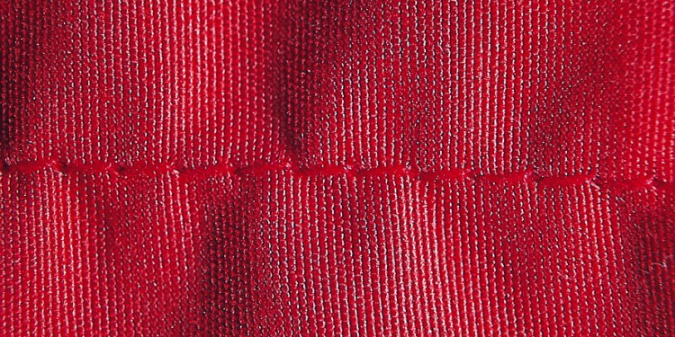Close-up of a red fabric showing seam puckering